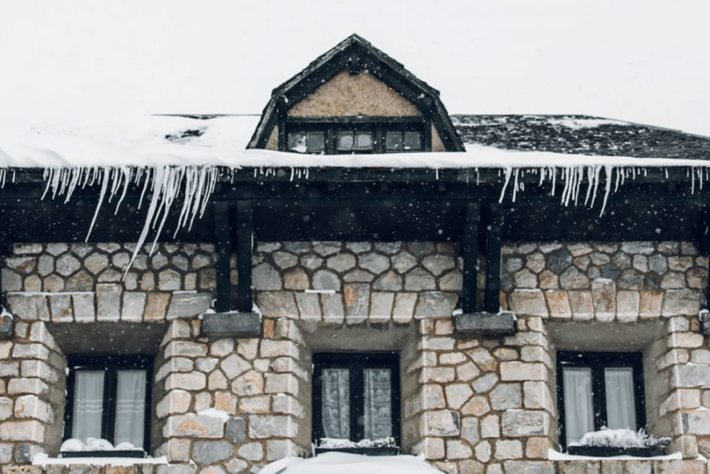stone house with snow all over the roof