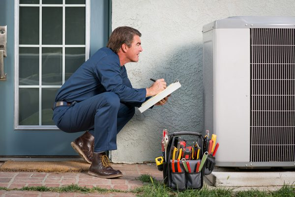 man holding clipboard inspecting a condensing unit outside